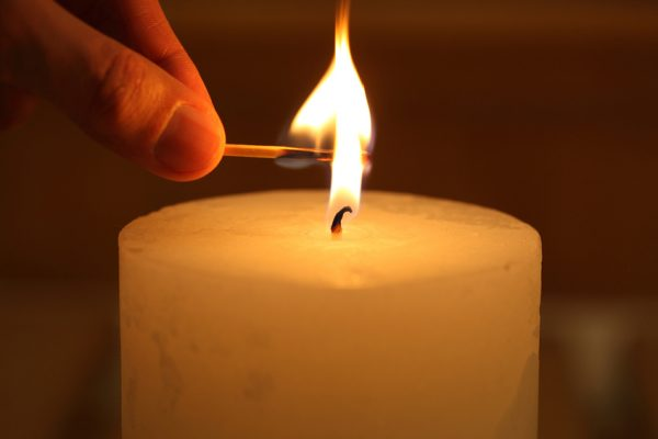 hand with a match lights a candle